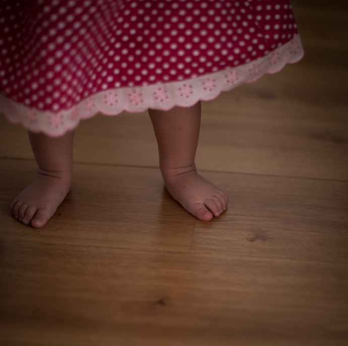 baby feet and a pink polka-dot dress with white trimmed hem