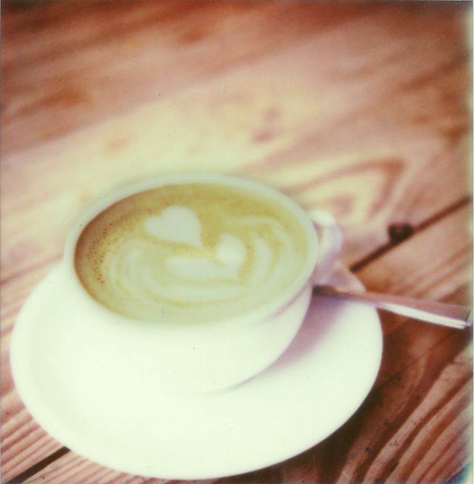 polaroid image of a flat white coffee sitting on a wooden table. copyright leonie wise