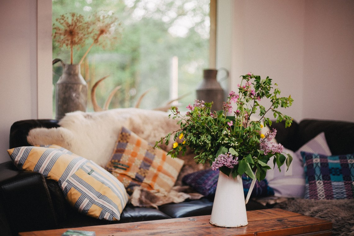 Fforest camp dining room - sofa and coffee table with flowers. By Leonie Wise