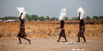 Three women carry a sack of food distributed on March 4, 2017, in Ganyiel, Panyijiar county, in South Sudan. South Sudan was declared the site of the world's first famine in six years, affecting about 100,000 people. More than three years of conflict have disrupted farming, destroyed food stores and forced people to flee recurring attacks. Food shipments have been deliberately blocked and aid workers have been targeted. / AFP PHOTO / Albert Gonzalez Farran - AFP / Albert Gonzalez Farran (Photo credit should read ALBERT GONZALEZ FARRAN/AFP/Getty Images)
