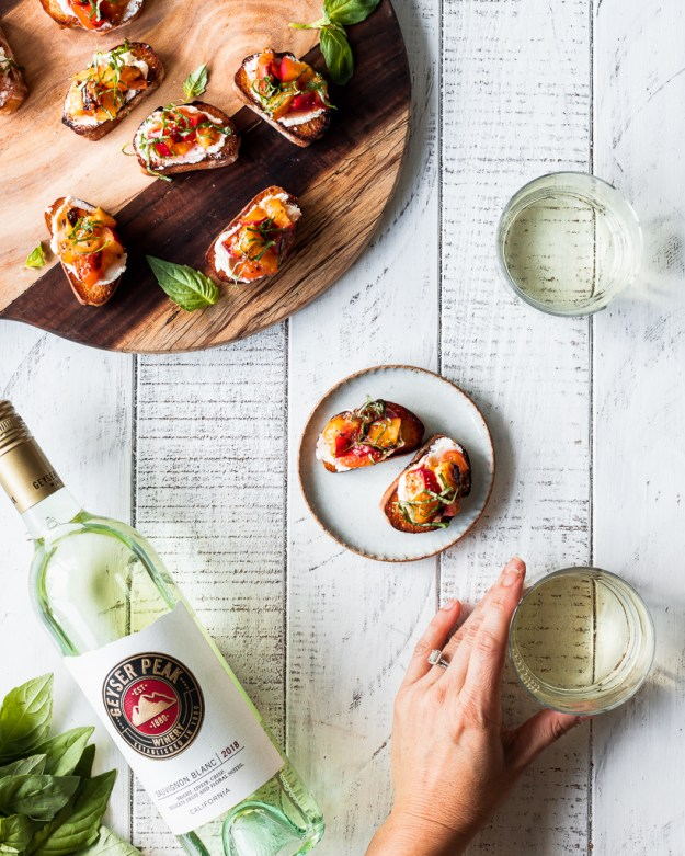 a wood board with grilled peach bruschetta and a hand reaching for a glass of white wine