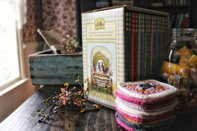 Little House on the Prairie books and stacked granny squares.