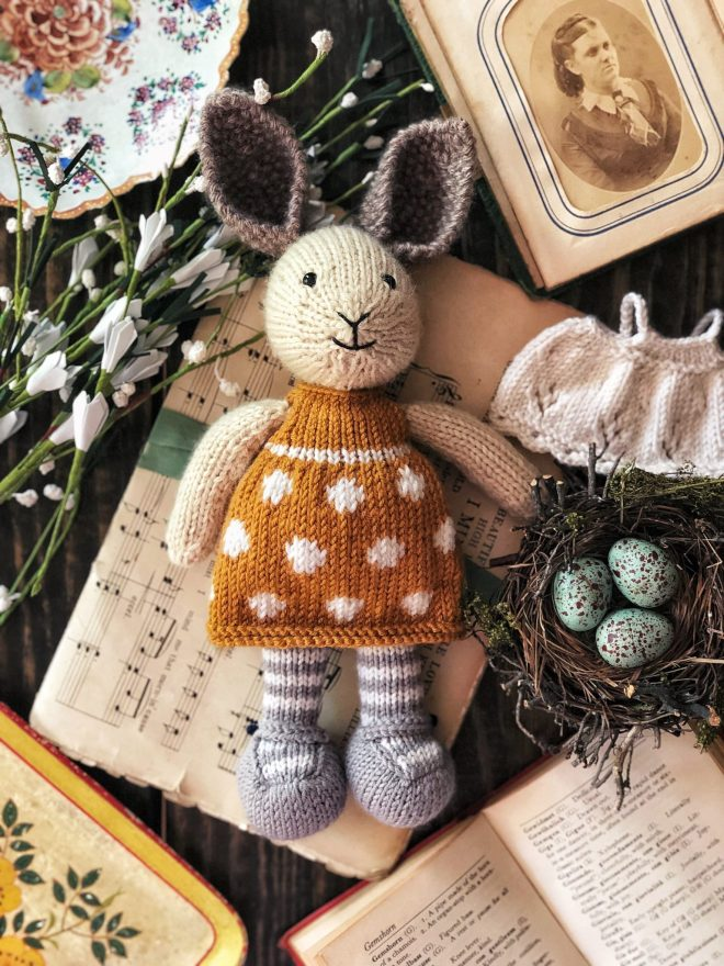 Knitted bunny in mustard yellow and white polka dot dress.