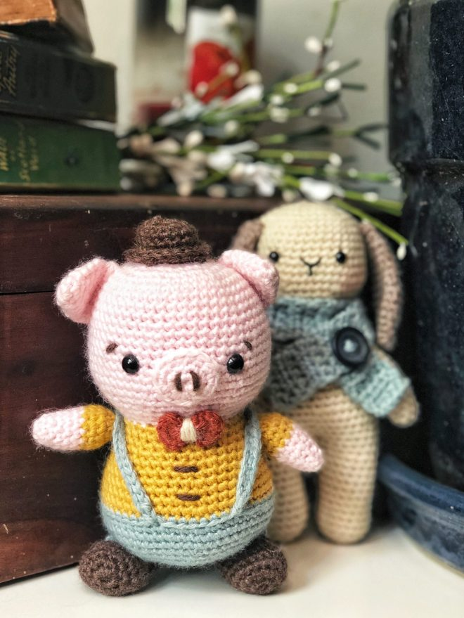 Amigurumi pig with a hat and suspenders standing in front of a crocheted bunny rabbit.