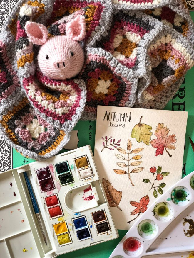 Autumn watercolor card, paint, knitted pig head, and granny squares.  Crafting Through the Crud.