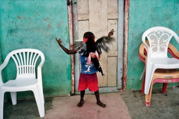 Un enfant joue avec une poule