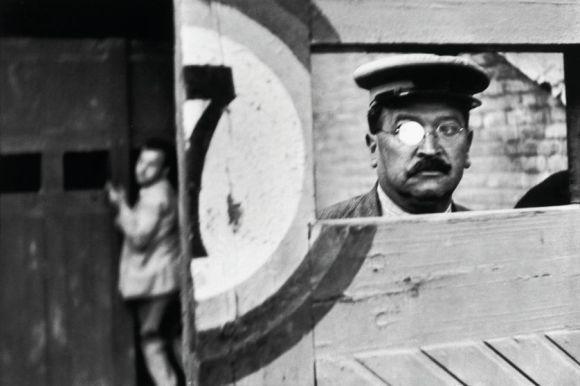 Une porte qui laisse apparaître un homme moustachu à lunettes