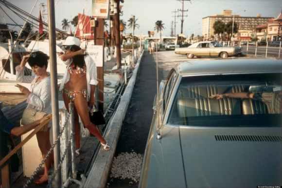 deux femmes regardent vers le port et bras d'un homme dans une voiture