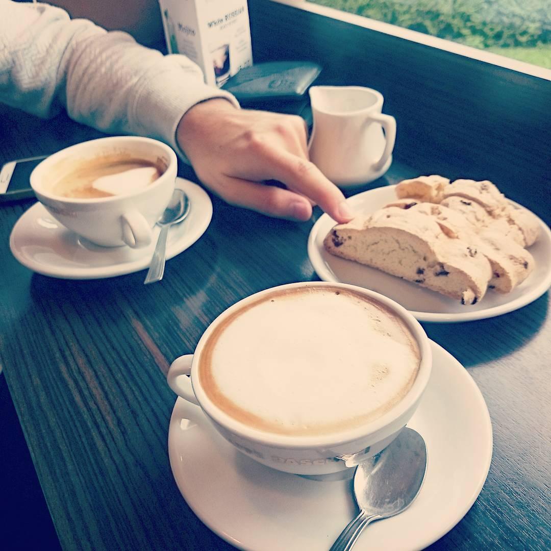 dwie kawy, ciastko i jego ręka