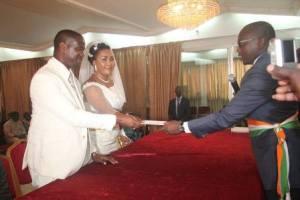 Le couple Okoué, recevant le livret de mariage des mains du sixième adjoint au maire