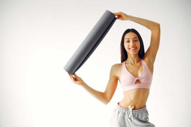 image d'une femme qui tien un tapis de yoga