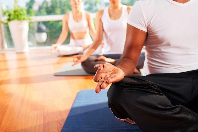 trois personnes assisent sur des tapis de yoga qui méditent