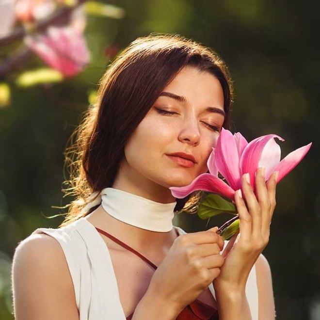 image femme qui sent une fleur