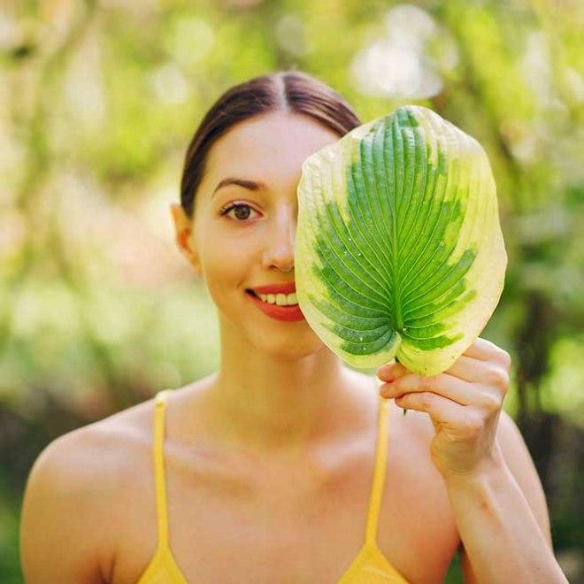 image femme derrière une feuille verte