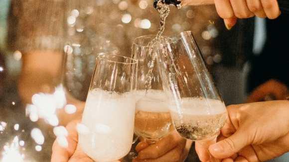 gute vorsätze person pouring champagne on champagne flutes