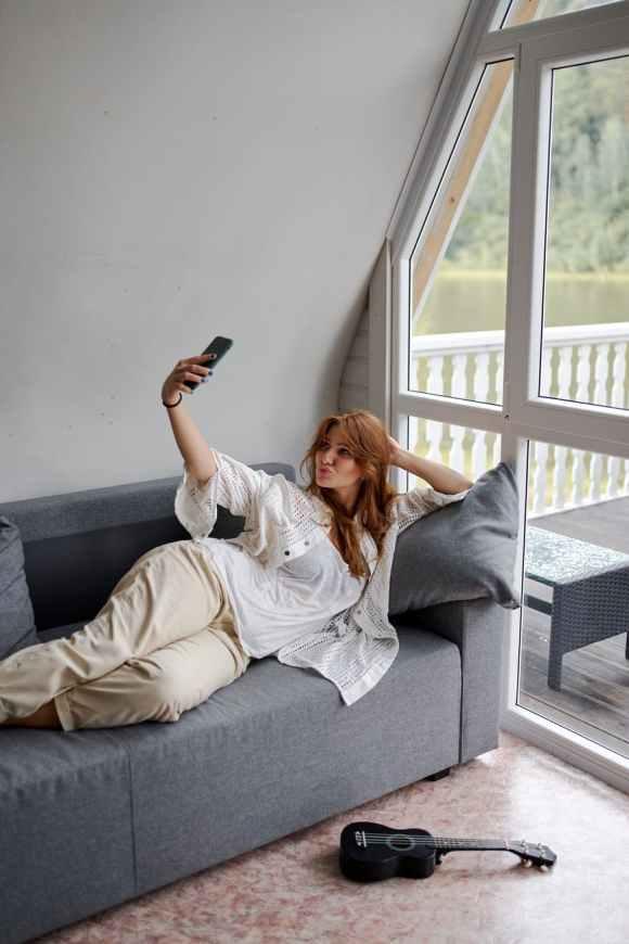 iPhone Foto drehen  woman on grey sofa taking selfie
