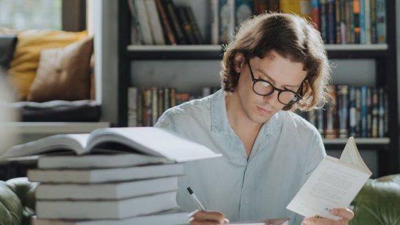 man in white dress shirt reading book
