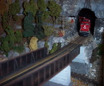 A train emerging from a tunnel onto a short rail bridge.
