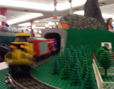 A lego caboose heading into a tunnel.