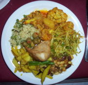 My first plate; some rice, olives, bean salad, curried veggies,  sprouts, a samosa, and curried potatoes.  Yum!