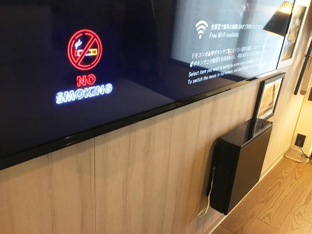 モクシー大阪新梅田,客室,ゲストルーム,リビングルーム,テレビの下の壁にミニ冷蔵庫が設置されている,Moxy Osaka Shin Umeda,