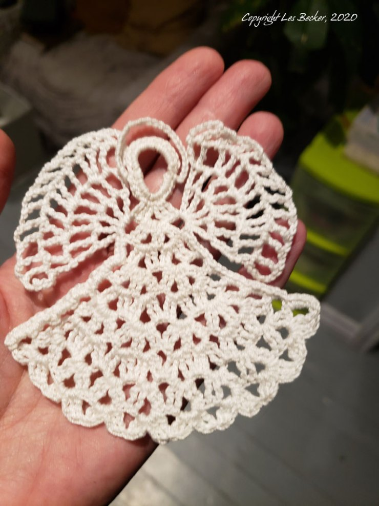 White crocheted Angel Christmas Tree Ornament in creator's hand