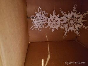 Crocheted snowflake ornaments hanging in glittering box