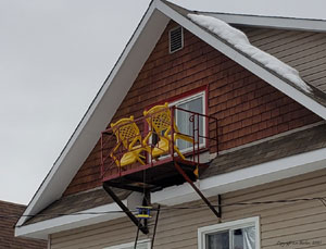 Two Yellow lawn chairs hanging precariously from an attic fire escape-on-Balcony2021