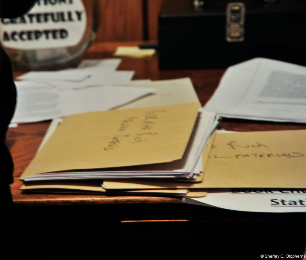Image of archival folders on a table labeled Adrienne Rich materials