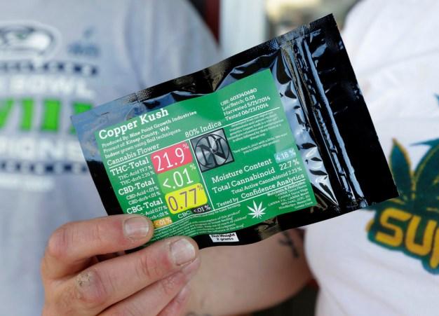 Julian Rodriguez, de Everson, Washington, tient son paquet de deux grammes de marijuana récréative en dehors Top Shelf cannabis, le mardi 8 Juillet 2014 à Bellingham, Washington, le premier jour de ventes légales de l'État. (Photo par Ted S. Warren / AP Photo)