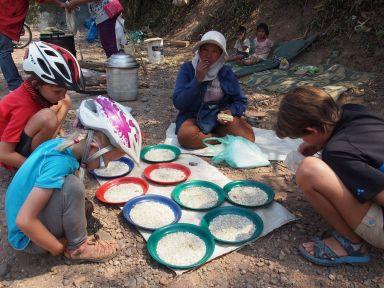 Tiens des femmes vendent du riz sur le bord de la route...