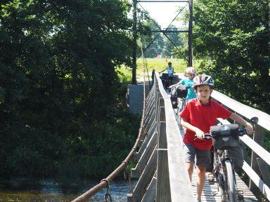 Passage d'un pont suspendu au-dessus de la rivière.