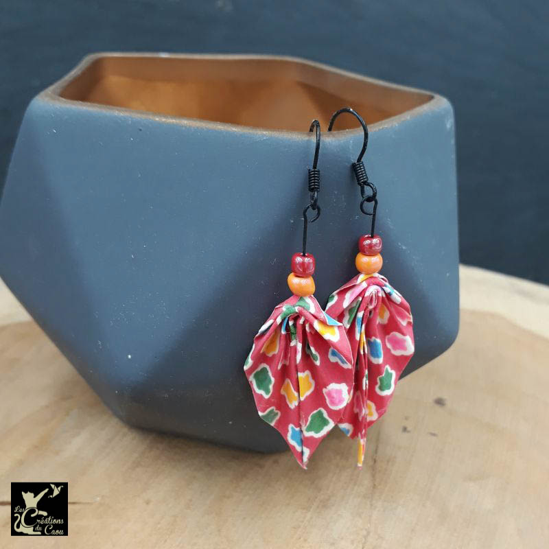 Boucles d'oreilles en origami. Le pliage est une palme réalisée à partir d'un papier japonais rose-rouge et de petits motifs multicolores.