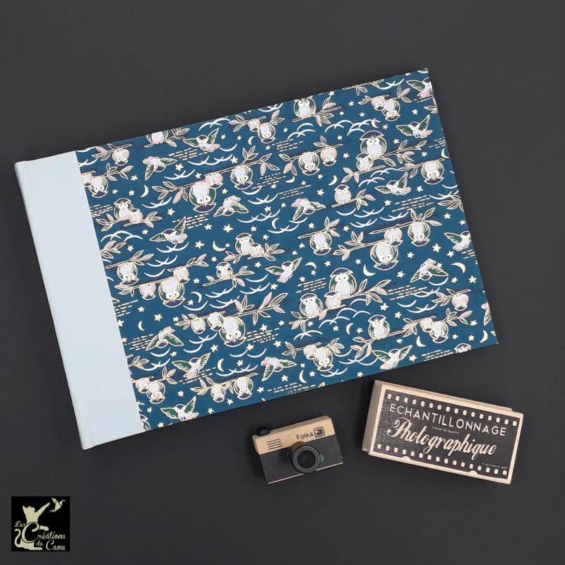 Album photos artisanal permettant d'accueillir 40 photos. Il est recouvert d'un élégant papier japonais bleu pétrole et orné de chouettes.