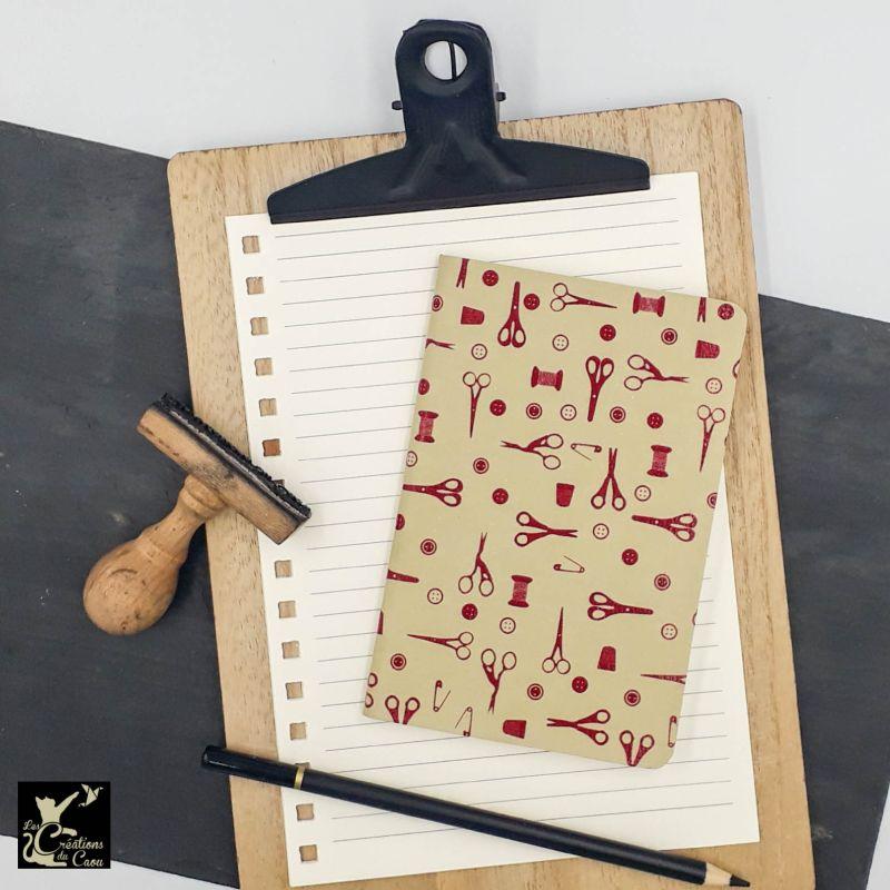 Carnet de notes au format A6. La couverture est recouverte à la main d'un papier indien de couleurs kraft orné d'éléments de couture rouge.