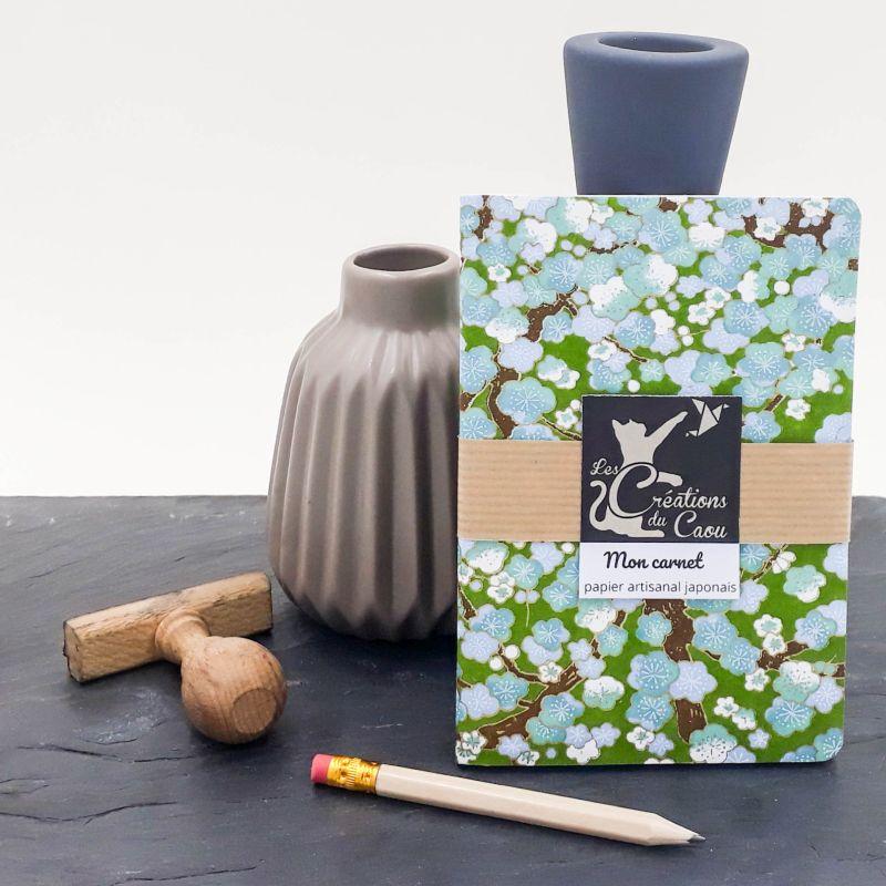 Carnet de notes au format A6. La couverture est recouverte à la main d'un papier japonais vert olive orné de fleurs de pruniers bleues.
