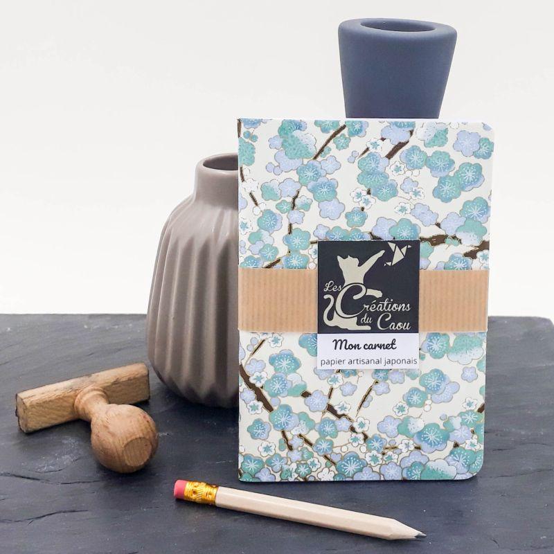 Carnet de notes au format A6. La couverture est recouverte à la main d'un papier japonais orné de fleurs de pruniers bleues.
