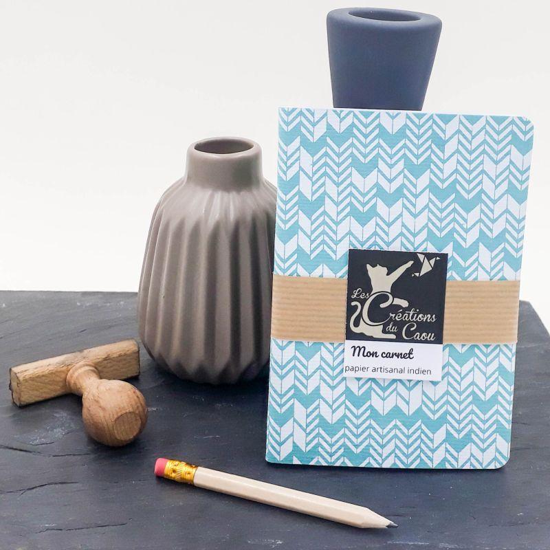 Carnet de notes au format A6. La couverture est recouverte à la main d'un papier indien bleu turquoise sur lequel sont dessinés des chevrons blancs.