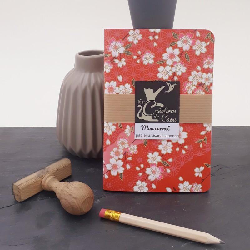 Carnet de notes au format A6. La couverture est recouverte à la main d'un papier japonais au fond rouge orné de motifs traditionnels et de sakura.