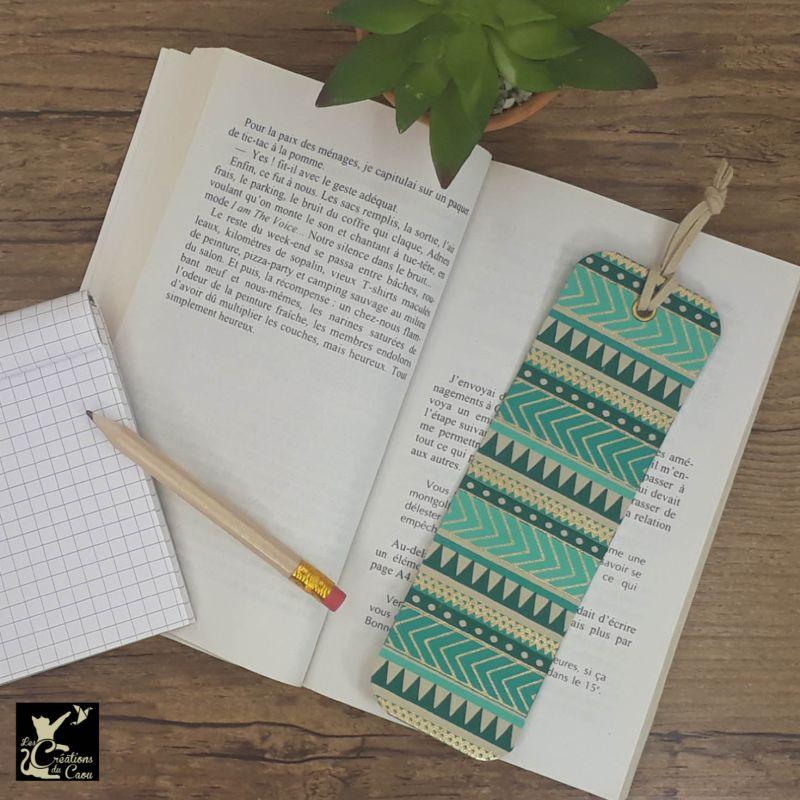 Ne perdez plus le fil de vos lectures ! Ce marque-page artisanal, recouvert d'un élégant papier indien au motif de bandes horizontales tuquoise, bleu canard, lin et or deviendra votre allié.
