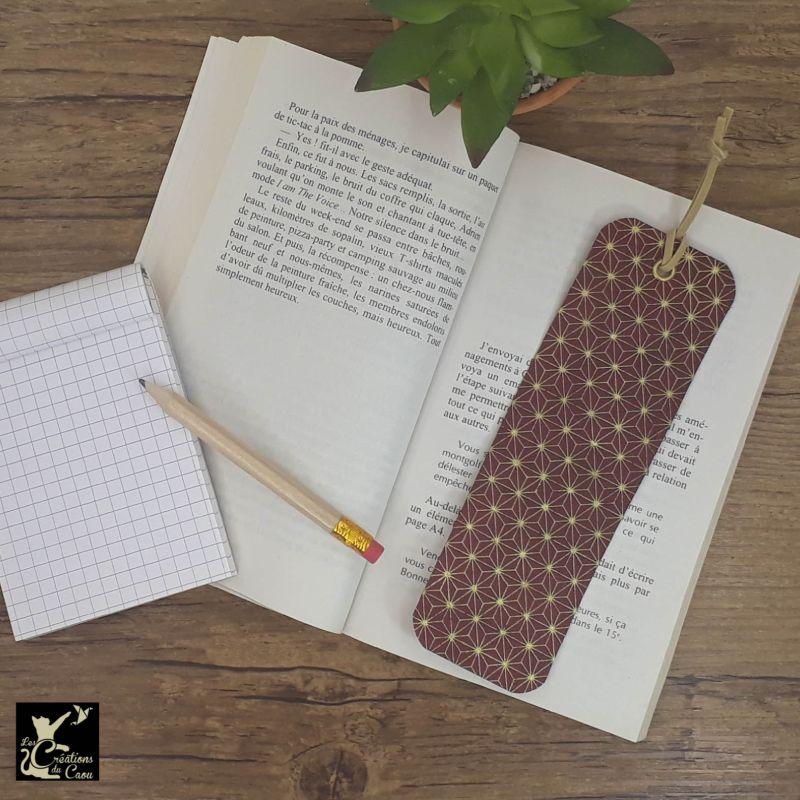 Ne perdez plus le fil de vos lectures ! Ce marque-page artisanal, recouvert d'un élégant papier japonais bordeaux au motif étoilé deviendra votre allié.