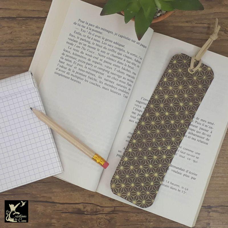 Ne perdez plus le fil de vos lectures ! Ce marque-page artisanal, recouvert d'un élégant papier japonais chocolat au motif étoilé deviendra votre allié.