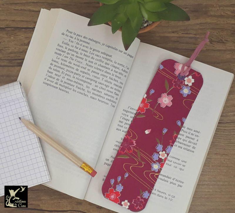 Ne perdez plus le fil de vos lectures ! Ce marque-page artisanal, recouvert d'un élégant papier japonais fuchsia orné de fleurs deviendra votre allié.