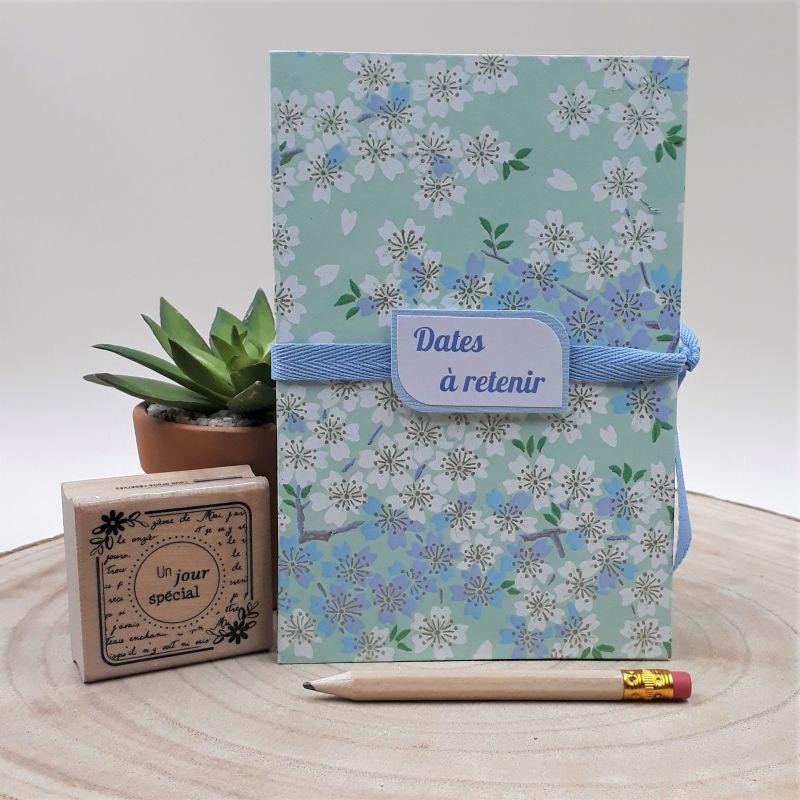 Calendrier des anniversaires recouvert d'un papier artisanal japonais vert d'eau au motif de fleurs de cerisiers blanches et bleues, entièrement réalisé à la main dans notre atelier de Lambersart (Lille).