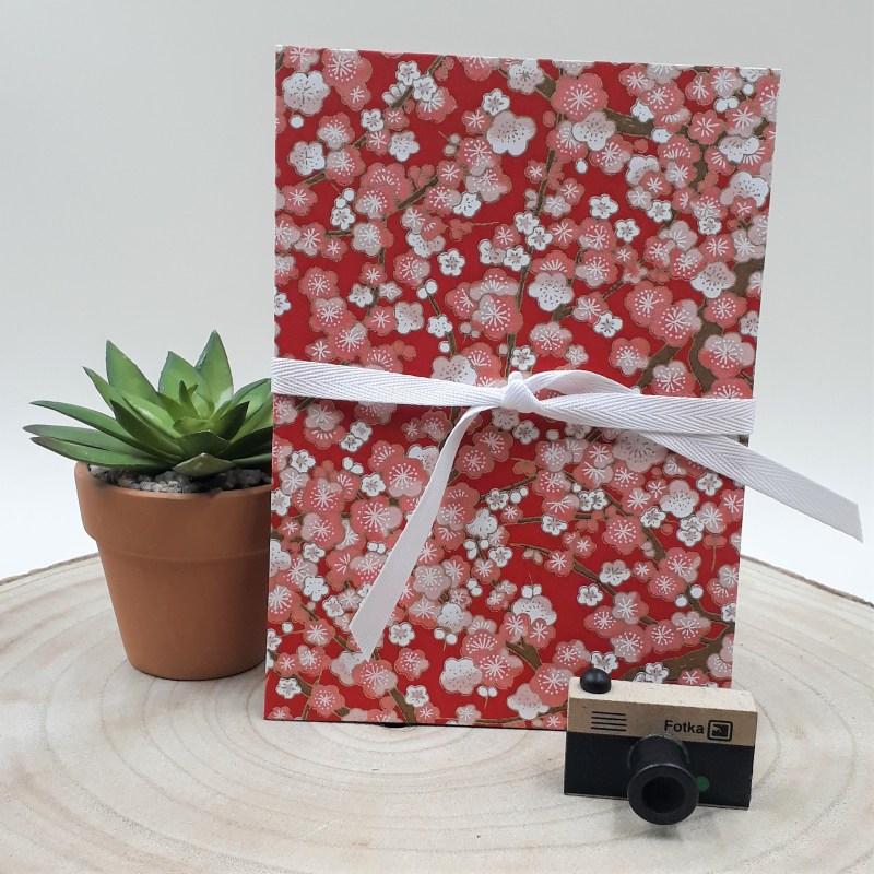 Album photo leporello réalisé à la main dans notre atelier de Lambersart (Lille), recouvert d'un papier japonais rouge au motif de fleurs de prunier.
