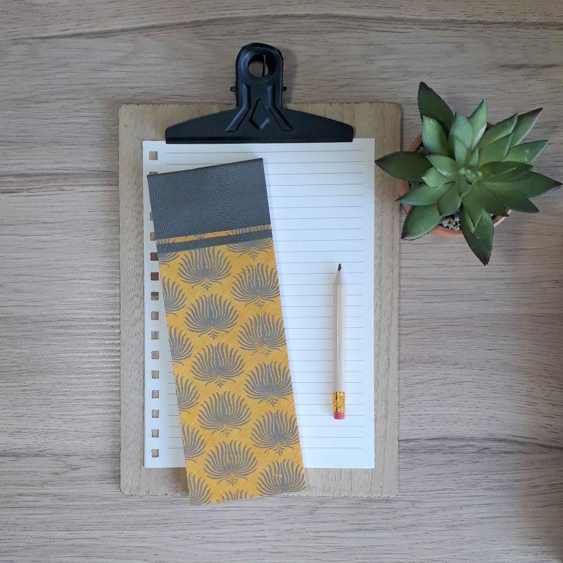 Bloc à listes réalisé à la main dans notre atelier de Lambersart (Lille), recouvert de papier népalais jaune moutarde au motif de palmes gris anthracite.
