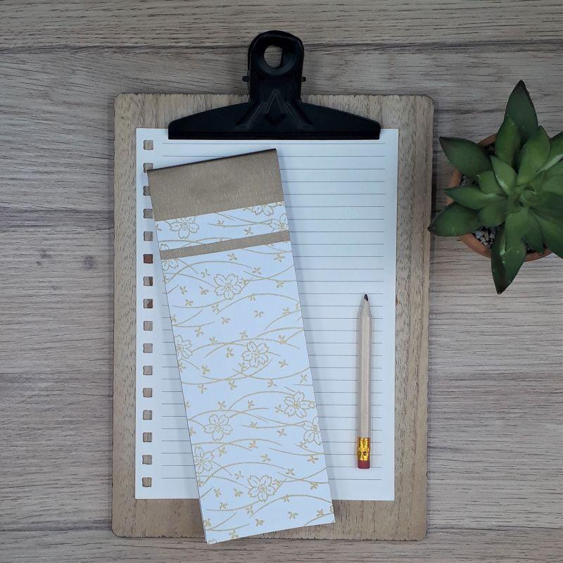 Bloc à listes réalisé à la main dans notre atelier de Lambersart (Lille), recouvert de papier japonais blanc au motif fleuri doré.