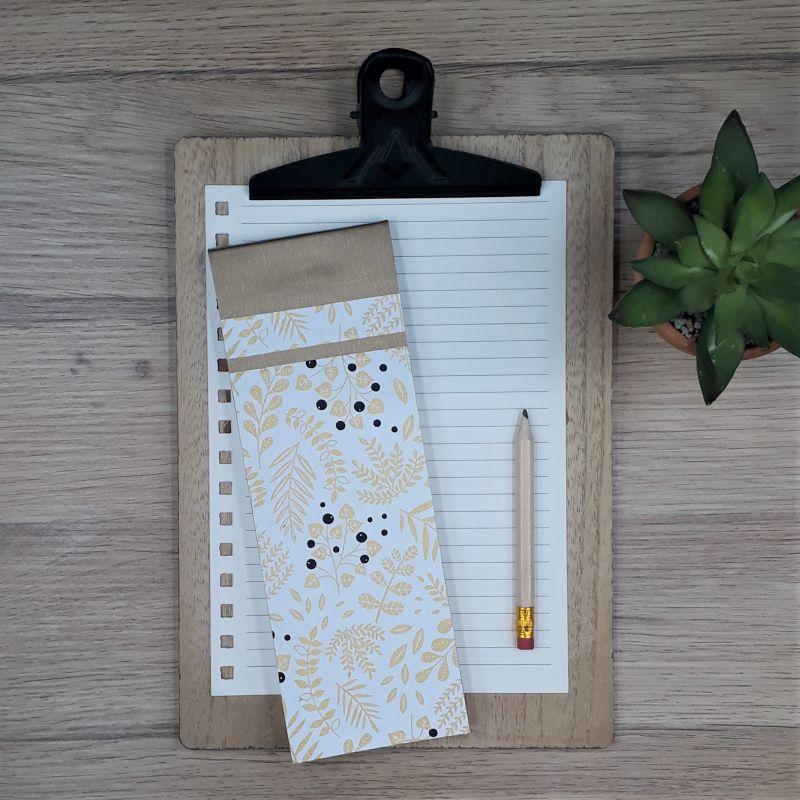 Bloc à listes réalisé à la main dans notre atelier de Lambersart (Lille), recouvert de papier japonais blanc au motif de végétaux dorés et de baies noires.