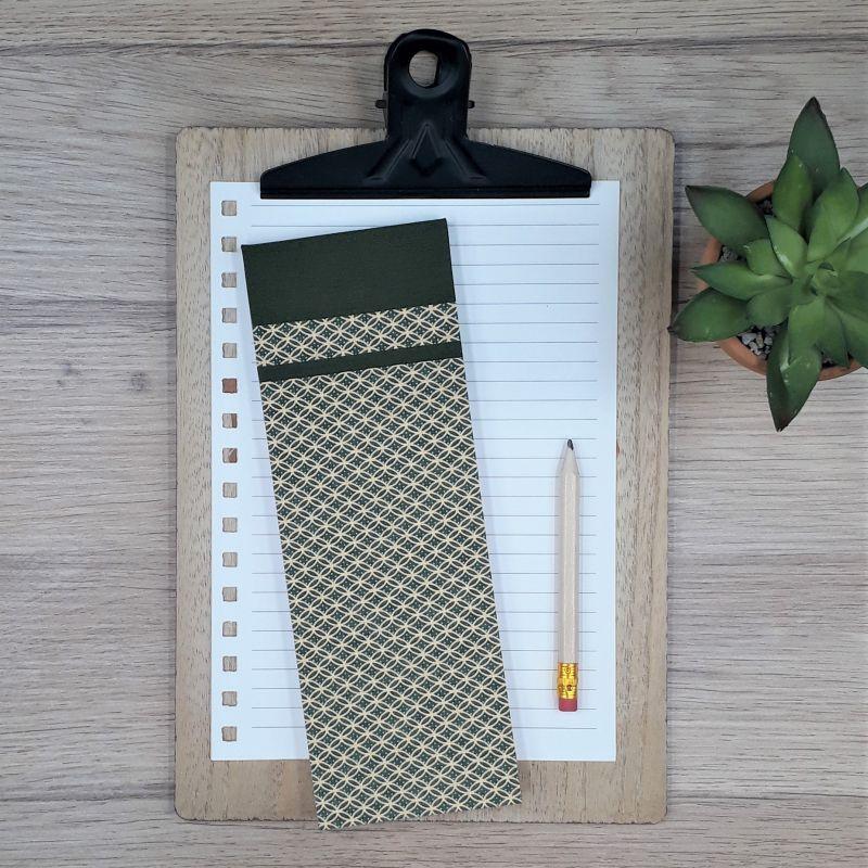 Bloc à listes réalisé à la main dans notre atelier de Lambersart (Lille), recouvert de papier japonais vert olive foncé orné de motifs géométriques dorés.