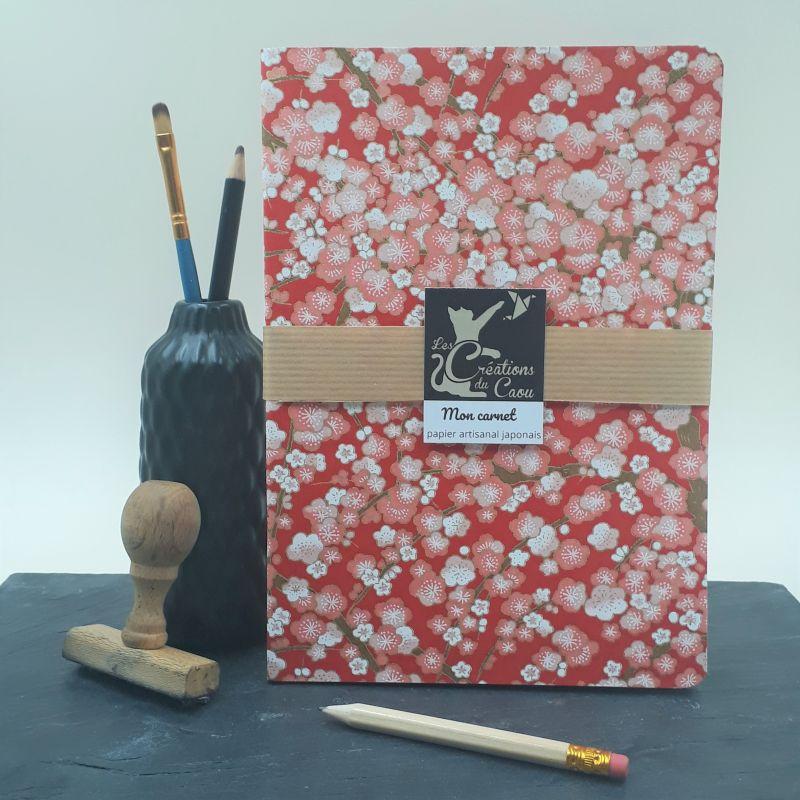 Carnet A5 recouvert à la main d'un papier artisanal japonais rouge orné de fleurs de pruniers rose et blanches.